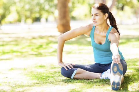 Sporty Woman Stretching On Grass In Park.jpg